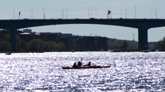 3 person kayaking in the river with ray of lights on the water-city background Stock Footage