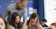 4K School children working at their desks in classroom & teacher helping them Arkistovideo