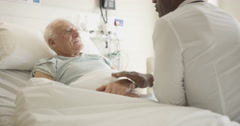 4K Friendly doctor comforting elderly patient at his bedside Stock Footage