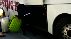 Tourists putting their luggage in bus luggage compartment-help of the bus driver - stock footage