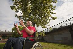 Man in wheelchair with ball Stock Photos