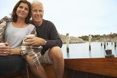 Middle aged couple cuddling on old boat Stock Photos