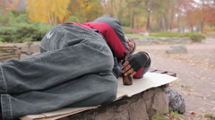 Drunk alcoholic sleeping on bench with empty bottle in hand, insolvent person - stock footage