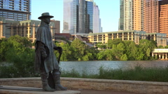 Stevie Ray Vaughan Statue in Front of Downtown Austin, Texas & Colorado River Stock Footage