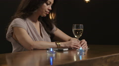 Sad and troubled woman sitting alone at a bar - stock footage