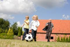 grandfather and kids playing football - stock photo