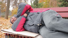 Male addicted to alcohol sleeping on bench, drunk man suffering from hangover - stock footage
