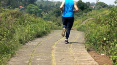 Young man jogging on path in country, super slow motion 240fps Stock Footage