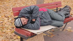Lonely poor man lying on bench, miserable bum suffering from hunger and cold - stock footage