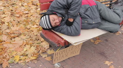 Generous young lady kindly giving charity money to poor man sleeping on bench Stock Footage