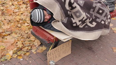 Miserable bum sleeping on bench with sign asking for help, homeless person Stock Footage