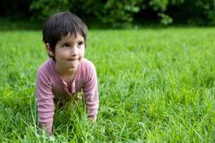 Girl crawling on all fours through grass Stock Photos