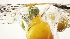 Lemon, lime and oranges falling into water in slow motion. Stock Footage