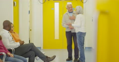 4K Senior couple talking to doctor & getting good news in hospital waiting area Stock Footage