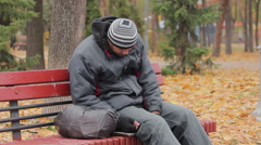 Male drinking addict sleeping on bench in autumn park, alcohol abuse problem - stock footage