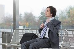 Businessman on bench, adjusting tie Stock Photos