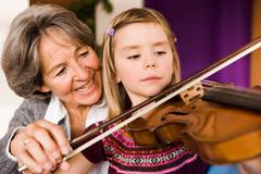 Grandma teaching grandchild music Stock Photos