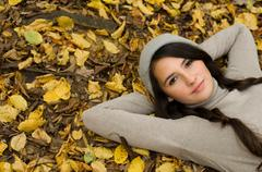 girl with pigtails lying on leaves - stock photo