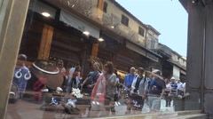 Ponte Vecchio tourists stroll, reflected in shop window Stock Footage