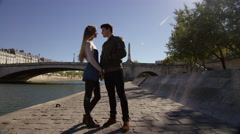 Couple sneak a kiss while taking a walk by the river. Stock Footage
