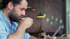 Man drinking coffee in trendy coffee shop, while checking his tablet Stock Footage