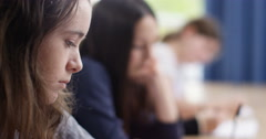 4k, Students in school uniform taking exam at desk in a classroom. Slow motion. Stock Footage