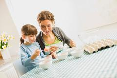 Mother and child coloring Easter eggs Stock Photos