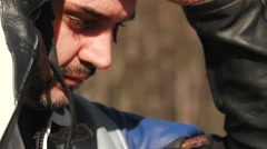 Close up on motorcycle driver taking off his helmet Stock Footage