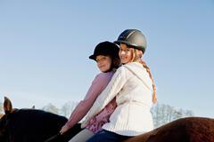 Two girls on a horseback Stock Photos