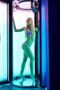 Image of leggy blonde tans in tanning booth Stock Photos