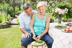 Mature woman peels pods,partner looks on - stock photo