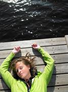 Woman laying down on a deck Stock Photos