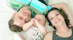 Happy family. Mom dad and six month old baby. Family lying in bed and looking at Stock Footage