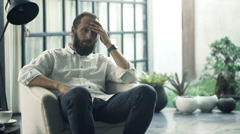 Sad, unhappy man sitting on armchair in living room at home   - stock footage