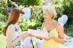 woman offers present to mature woman. - stock photo