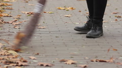 Feet of street cleaner sweeping autumn park, person working hard for low wage - stock footage