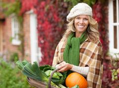 Smiling woman with seasonal vegetables - stock photo