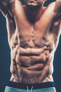 Strong Athletic Man Fitness Model Torso showing six pack abs. is - stock photo