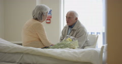 4K Senior couple in hospital room, man visiting his sick wife & giving flowers. Stock Footage