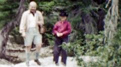 1959: Dad son throwing rocks in cowboy hat at cameraman. Stock Footage