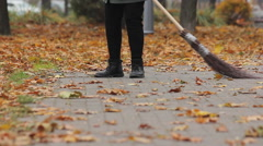 Street cleaner in shabby boots sweeping dry leaves in autumn park, low paid job Stock Footage