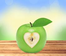 Fresh green apple with heart on wooden table over nature background Stock Photos