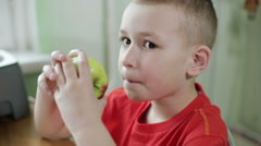 A boy in a red shirt eating an apple at the kitchen. Small boy licks his lips. Stock Footage