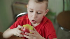 Small beautiful boy with big eyes eating an apple appetizing. Stock Footage