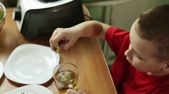 A boy in a red t-shirt dunks a tea bag in a cup of boiling water. Stock Footage