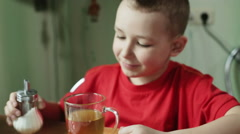 Little boy in the red shirt is mixing a sugar in the cup of tea  via the spoon. Stock Footage