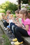 Children enjoying popsicle outdoors Stock Photos