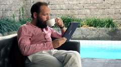 Young man on sofa reading article on tablet and drinking coffee on patio - stock footage
