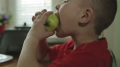 The little boy with a big eyes is biting an apple. Stock Footage