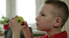 The boy in the red shirt is chewing an apple and looking ahead. Stock Footage